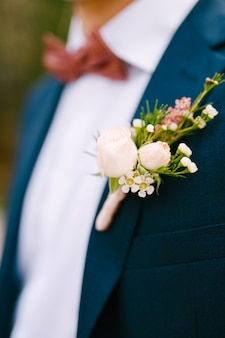 Мужчина в синем пиджаке, белой рубашке, бордовом галстуке-бабочке и с бутоньеркой из маленьких роз