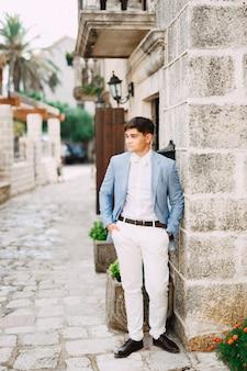 蝶ネクタイをした青い上着を着た男が古代の建物の前に立ち、手をつないでいる