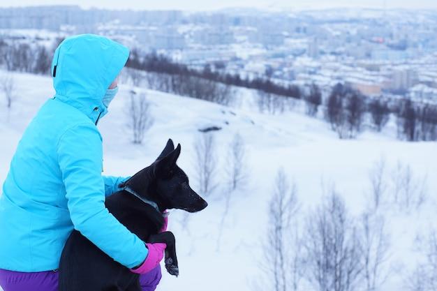 フードをかぶった青いジャケットを着た男性と黒い犬が冬に座って自然を眺めています。