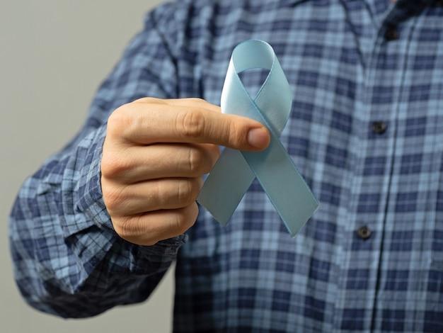Мужчина в голубой клетчатой рубашке держит голубую ленту. знак борьбы с раком простаты. понятие о медицине и средствах здравоохранения.