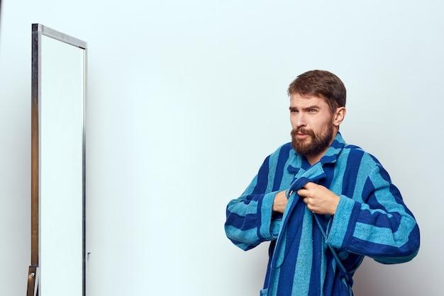 Мужчина в синем халате рассматривает себя в зеркало в яркой комнате. обрезанный вид.