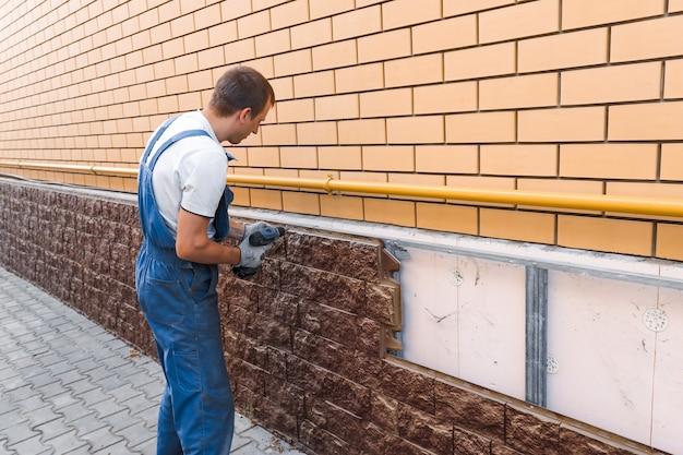 파란색 유니폼을 입은 남자가 도구 나사로 집 야외 서비스 작업자의 벽을 수리하고 있습니다