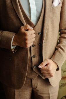 Мужчина в коричневом костюме-тройке. руки держатся по бокам куртки. крупный план