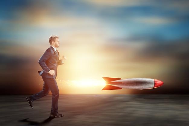 비즈니스 정장을 입은 남자, 사업가가 로켓을 따라 잡고있다.