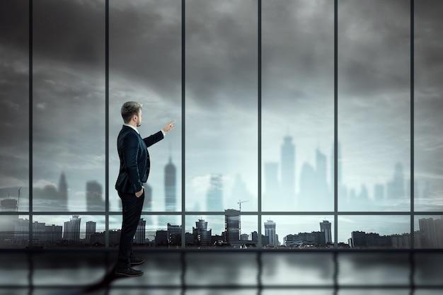 ビジネススーツを着た男性、ビジネスマンが街を見下ろす大きな窓の背景に立って、遠くを見る