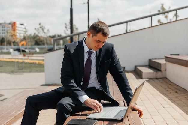 ビジネススーツとラップトップの男がベンチに座っています。ラップトップを持つビジネスマン。