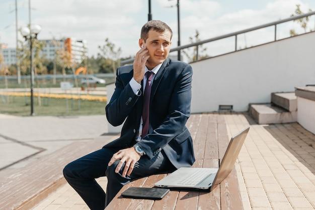 Мужчина в деловом костюме и ноутбуке сидит на скамейке. бизнесмен с ноутбуком.
