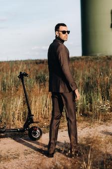 ビジネススーツと緑のゴルフシャツを着た男性が、フィールドと青い空を背景に電動スクーターの隣に立っています。