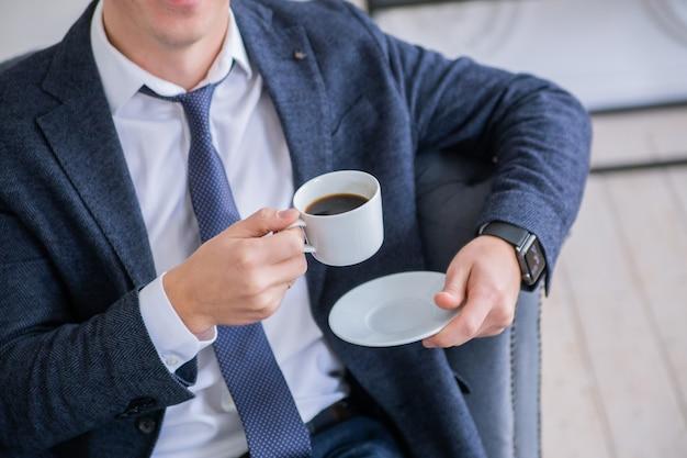 비즈니스 정장을 입은 남자가 손에 커피 한 잔을 들고 있다