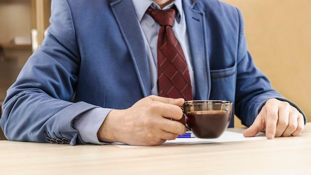 비즈니스 정장을 입은 남자가 손에 뜨거운 커피 한 잔을 들고 있습니다. 아침 사업가입니다. 확대.