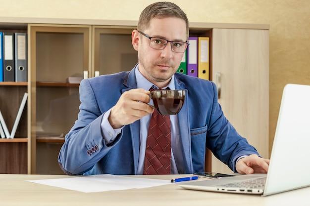 비즈니스 정장을 입은 남자가 손에 뜨거운 커피 한 잔을 들고 회사원의 아침