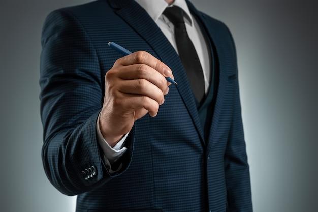 ビジネススーツを着た男性がボールペンで手を差し出し、空中に書いています。ビジネスコンセプトの在庫。クローズアップ、コピースペース。