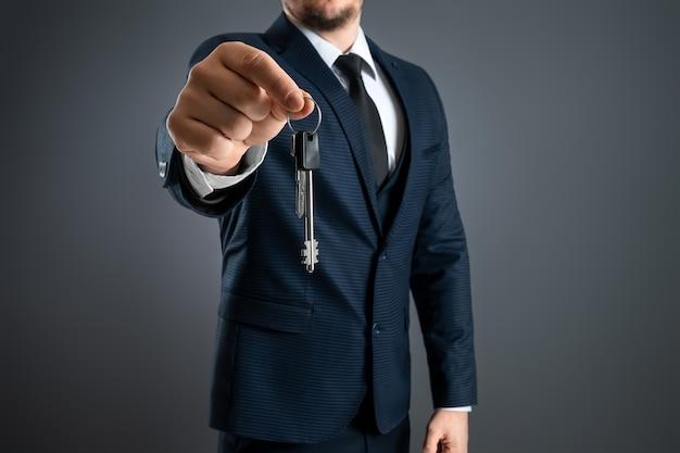 ビジネススーツを着た男性が鍵を手に持っています。不動産業者、住宅ローン、あなたの家、住宅ローンの概念。スペースをコピーします。