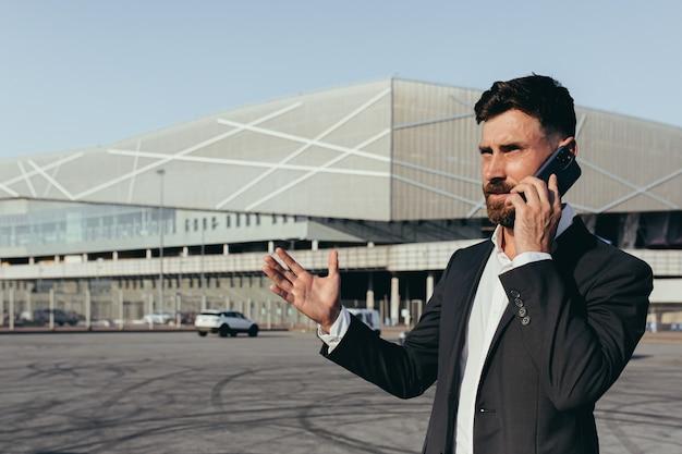 비즈니스 정장을 입은 남자가 사무실 근처에서 전화 통화를 하고 있다