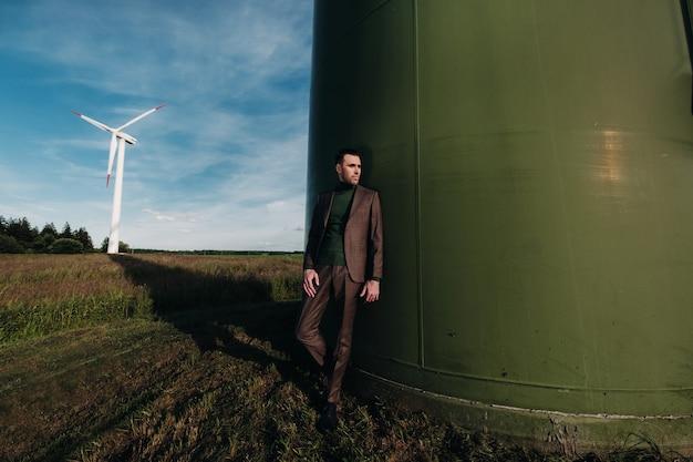 緑のゴルフシャツを着たビジネススーツを着た男性が、フィールドを背景に風車の横に立っています。