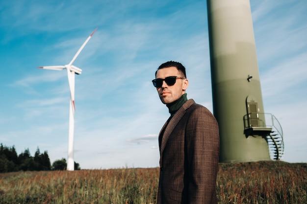 緑のゴルフシャツを着たビジネススーツを着た男性が背景に風車の横に立っています
