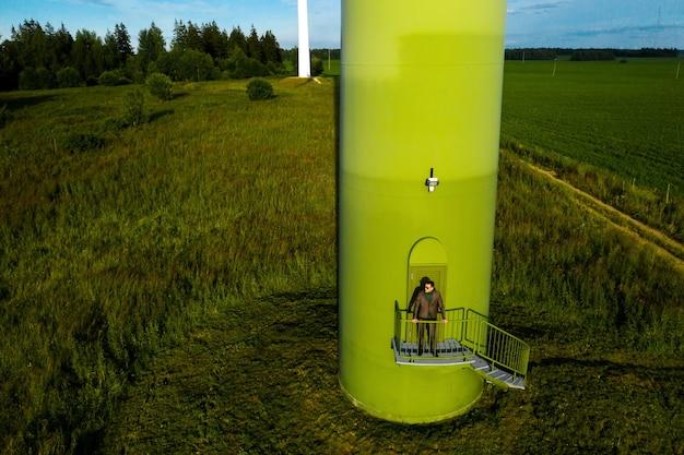 緑のゴルフシャツを着たビジネススーツを着た男性が、風車の横に野原と青い空を背景に立っています。
