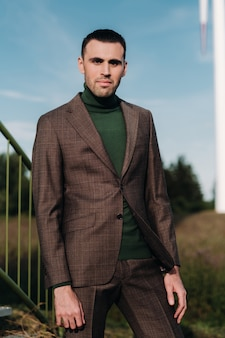 緑のゴルフシャツを着たビジネススーツを着た男性が風車の隣に立っています