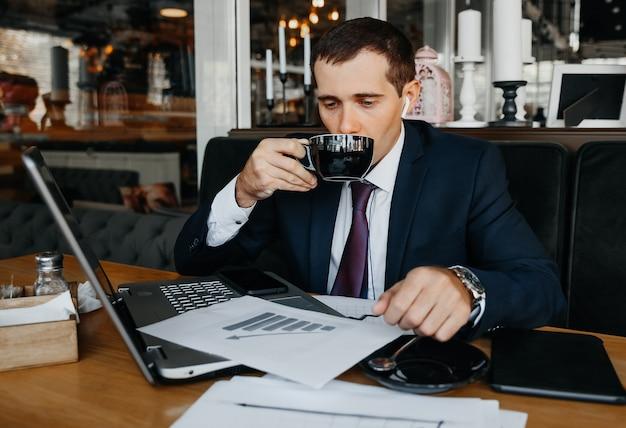 비즈니스 정장을 입은 남자가 카페에서 노트북 작업을 합니다. 노트북과 사업가입니다.