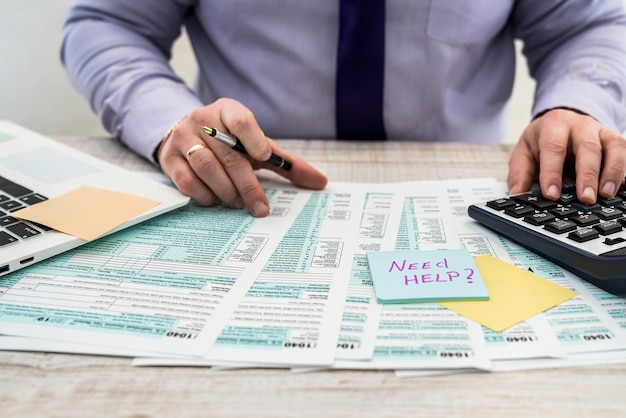 비즈니스 정장을 입은 한 남자가 사무실에서 1040 세금 양식을 작성합니다. 남성 손 직장에서 계산기로 종이에 채 웁니다. 회계 개념