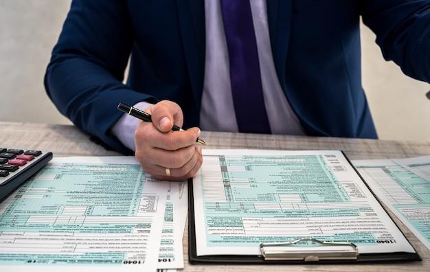 ビジネススーツを着た男性がオフィスで1040の納税申告書を作成します。男性の手は職場で電卓で紙に記入します。会計の概念
