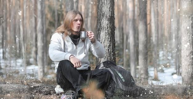 Мужчина в походе пьет чай. молодой путешественник разбил лагерь в лесу и приготовил завтрак на природе. натуралист пьет горячий свежий чай, приготовленный на открытом огне.
