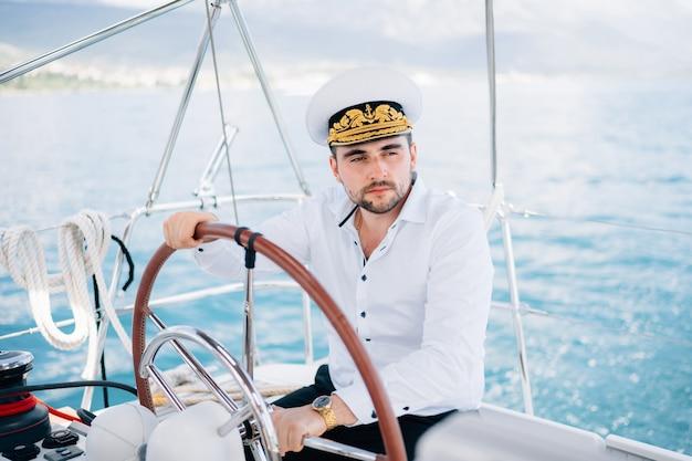 캡틴 모자를 쓴 남자가 바다 한가운데를 항해하는 요트의 키에 앉아 있다