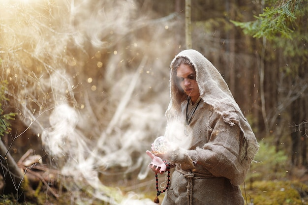 キャソックの男が水晶玉と本を持って暗い森で儀式を過ごす
