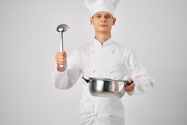 シェフの制服を着た男性が、鍋を手に持って料理のプロのレストランを調理しています。高品質の写真