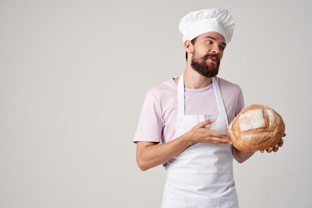 요리사 유니폼을 입은 남자가 손에 빵을 들고 요리를 하고 있다