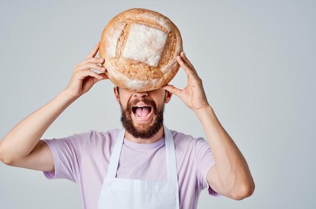 요리사 제복을 입은 남자가 손에 빵을 들고 주방 전문 산업
