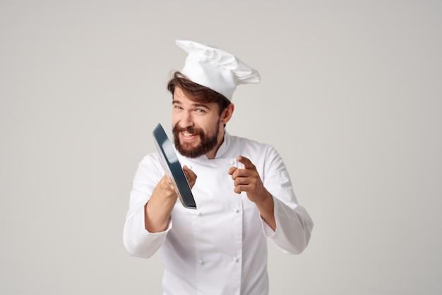 고립 된 배경에 프라이팬을 들고 요리사 유니폼을 입은 남자