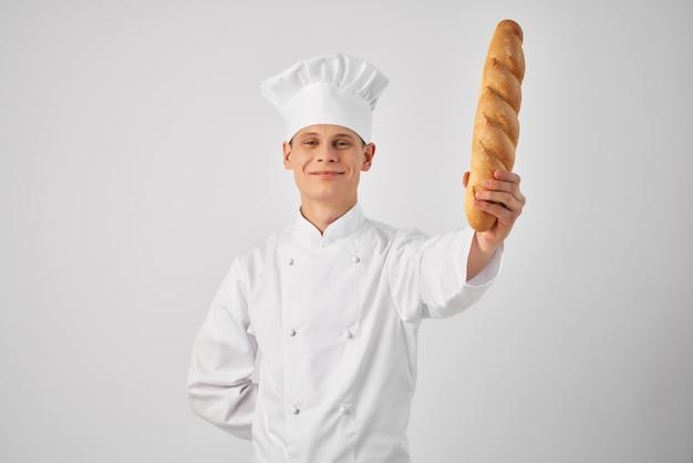 手にパンを持ったシェフの制服を着た男生鮮食品の仕事明るい背景