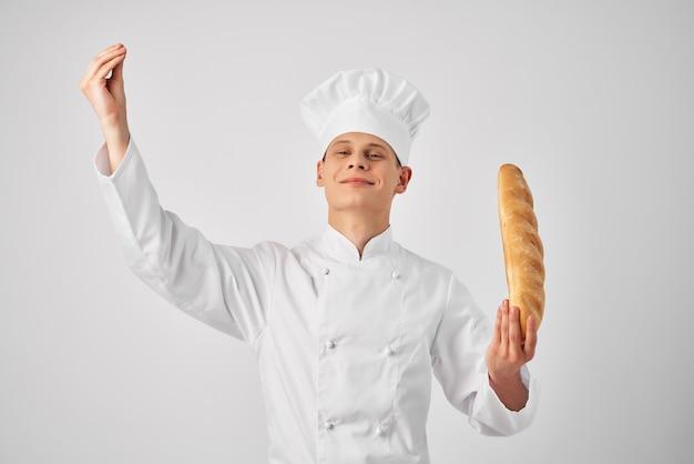 Мужчина в форме повара с буханкой в руках свежих продуктов работает на светлом фоне