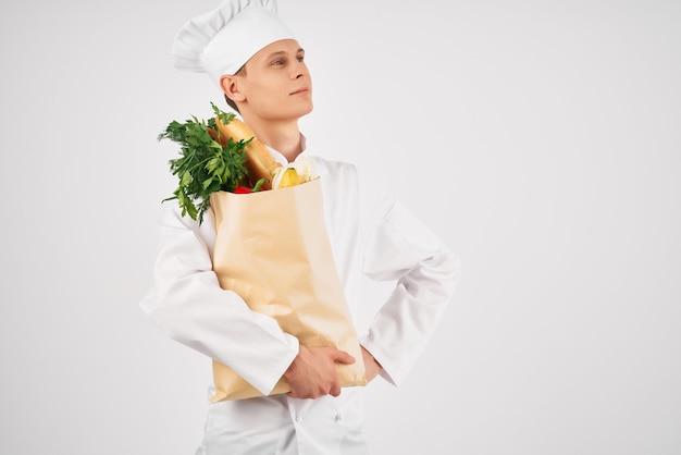 製品のパッケージを持ったシェフの制服を着た男性レストランのキッチンサービス