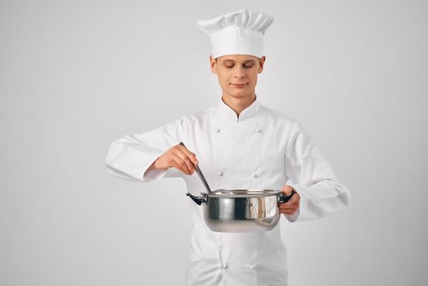 음식 레스토랑을 준비하는 손에 팬을 들고 요리사 유니폼을 입은 남자