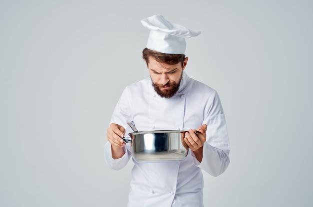Мужчина в форме повара с кастрюлей в руках дегустирует профессиональную еду в ресторане