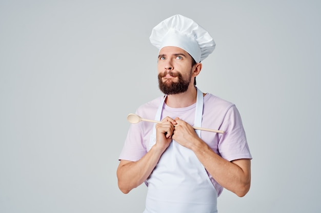 Мужчина в форме повара с ложкой в руках готовит эмоции