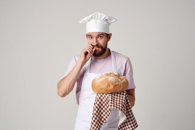 요리사 제복을 입은 남자가 손에 빵을 들고 베이킹 요리를 하고 있다