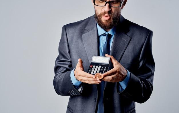 클래식 슈트를 입은 남자가 비트 코인 암호 화폐의 손과 동전을 제어합니다