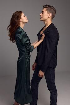古典的なスーツを着た男性は、灰色の背景にドレスを着た美しい女性を見ています。