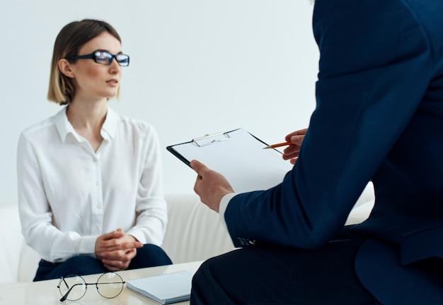 그의 손에 문서가있는 클래식 정장을 입은 남자와 실내 소파에 안경을 든 여자
