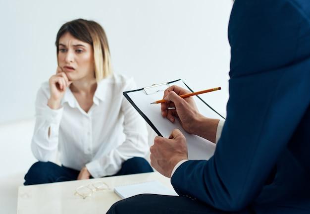 그의 손에 문서가있는 클래식 정장을 입은 남자와 소파에 감정적 인 여자