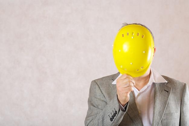 Мужчина в классическом костюме закрывает лицо защитным шлемом.