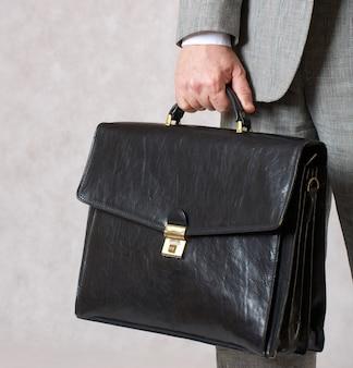 У человека в классическом костюме хранилась черная офисная кожаная сумка. крупный план. свободное место для текста.