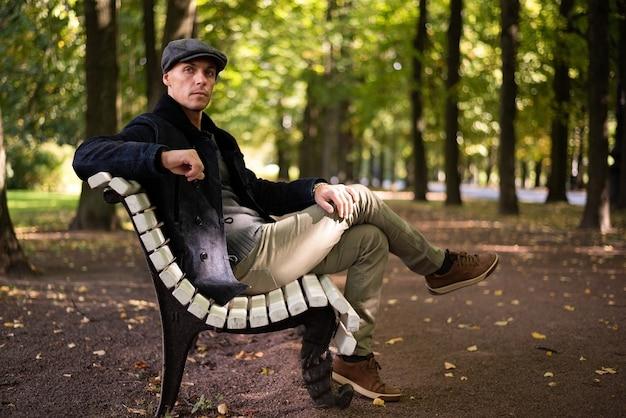 코트와 모자를 쓴 남자가 도시를 산책합니다. 고품질 사진