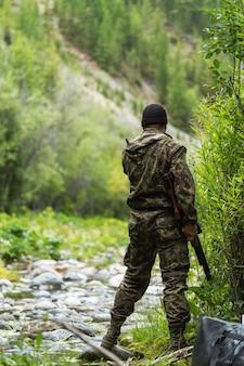 Мужчина в комбинезоне с винтовкой в руках смотрит вперед. утиная охота.