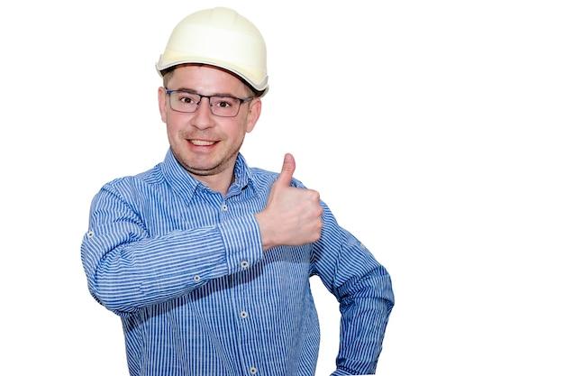 건설용 헬멧을 쓰고 흰색 외진 배경에 파란색 셔츠를 입은 남자가 손을 들고 엄지손가락을 보여줍니다. 준장. 빌더. 엔지니어. 사장.