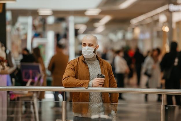 コロナウイルスの蔓延を防ぐためにフェイスマスクをかぶった男性が、ショッピングセンターで待っている間コーヒーを持っています。サージカルマスクのハゲ男が社会的距離を保っています。