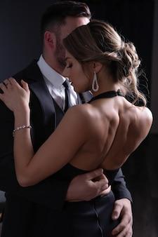 情熱のある男が彼を抱く若い女性のドレスのボタンを外す